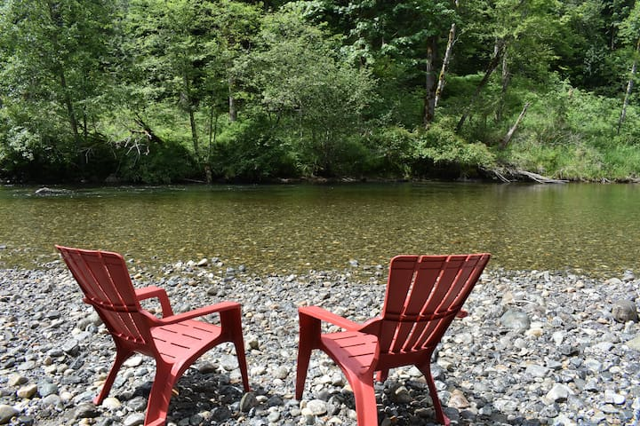 Relaxing at the river, shallow beach leads toward deeper swim hole on far side or a river float.