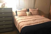 Clean bedroom with iron, ironing board, extra cover, and pillows.