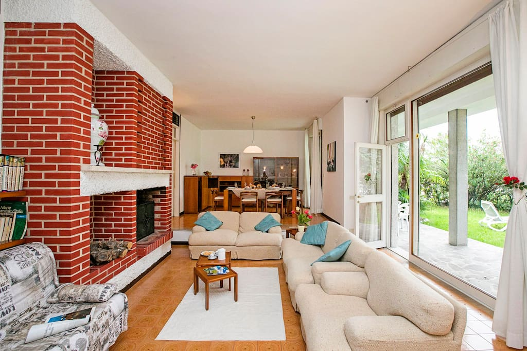 The spacious and bright living room with exit to the terrace and the garden