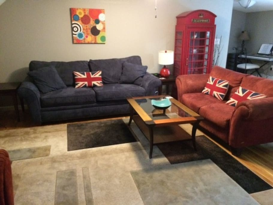 Large living room with queen sized Sleeper Sofa and two other couches.
