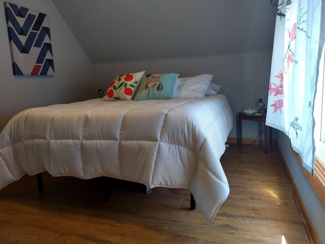 Clean queen-sized bed and a soft comforter with several pillow options