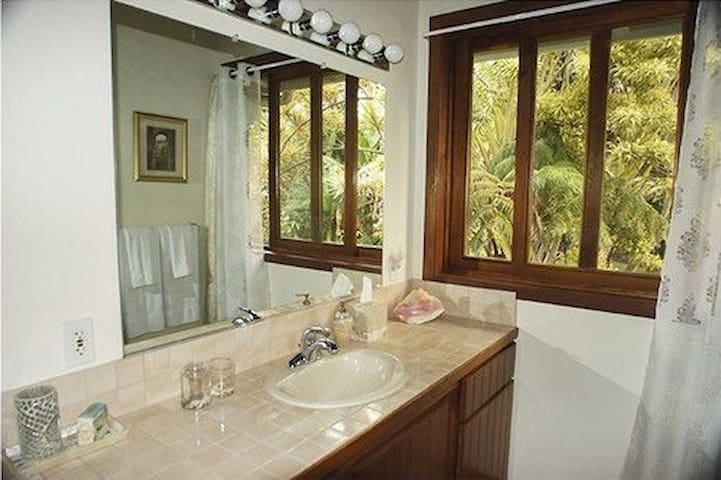 Your private bathroom overlooks the garden and pool.  The vanilla orchid may be blooming just out your window.  It has a full bathtub and shower head.  Luxury in the tropics.