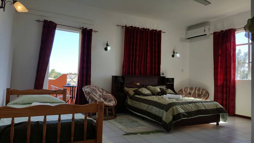 Bedroom with a double bed and a single bed with a balcony and ensuite