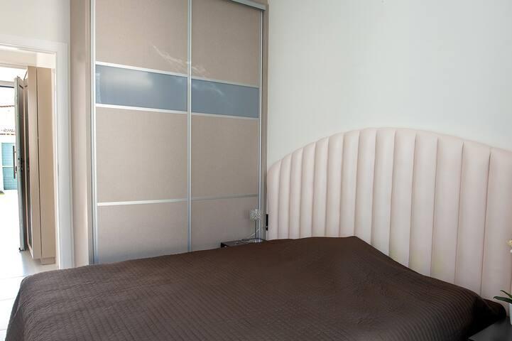 1 chambre au rez de chaussée avec 1 lit double, placard et 1 salle de bain avec évier, douche italienne, WC.