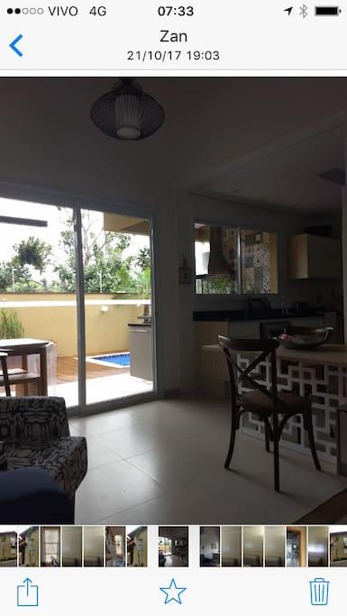 Sala e cozinha americana com vista da piscina e churrasqueira
