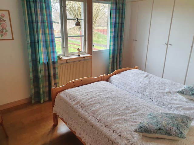 Sovrum med dubbelsäng och många garderober för förvaring,balkongdörr ut till uteplats med möbler och en rejäl grill och gungställning för barnen