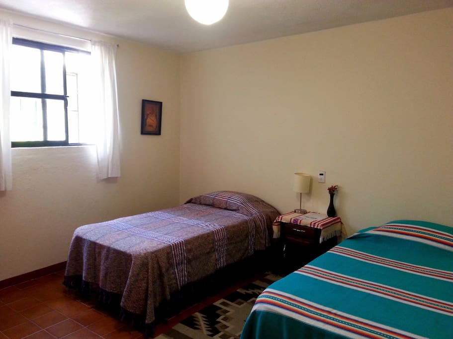 This room has two twin beds and a window overlooking the garden.