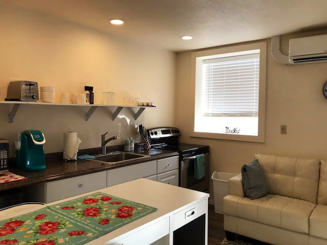 Kitchenette with full size smooth top range and oven, sink, coffee maker, microwave, toaster, and mini fridge.