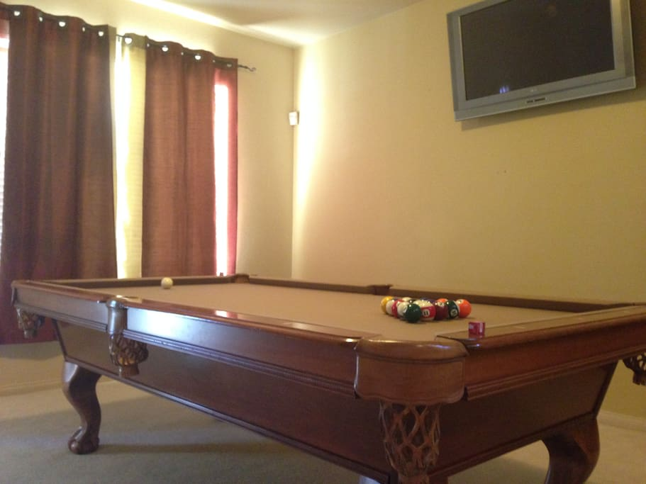 The pool table located in the entrance. It also comes with a mounted TV so you can stream from your phone to the TV while playing pool!