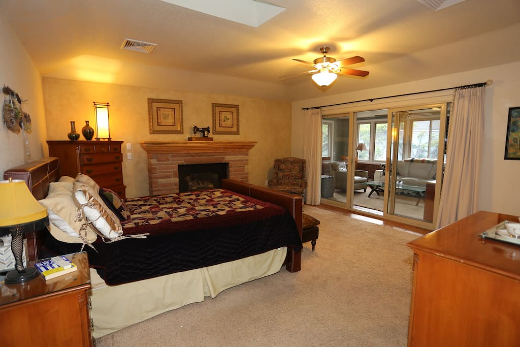Master bedroom, with fireplace, sky window, and slider doors openning to the private four season sunroom.