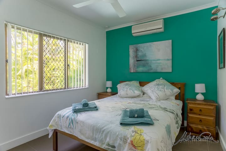 Bedroom 1. Queen size bed, air-conditioned, view over pool and garden.
