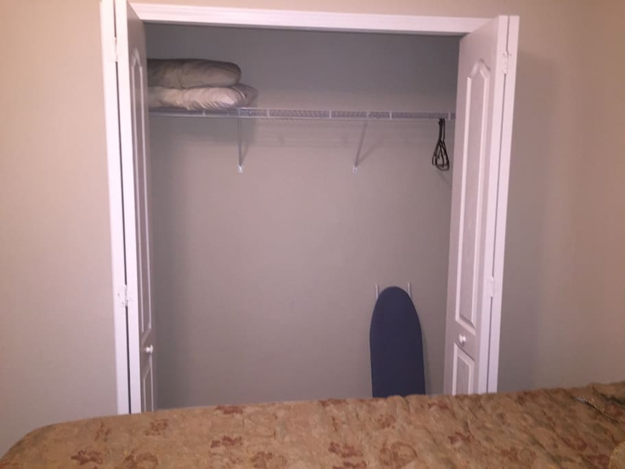 Closet with ironing board & extra pillows.