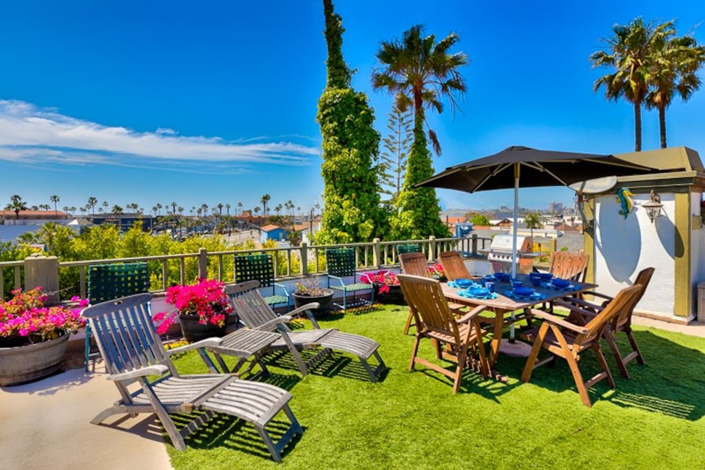 Rooftop deck boasts a dining table for al fresco dining, 2 lounge chairs, a bbq and a high top bar with fire pit built in