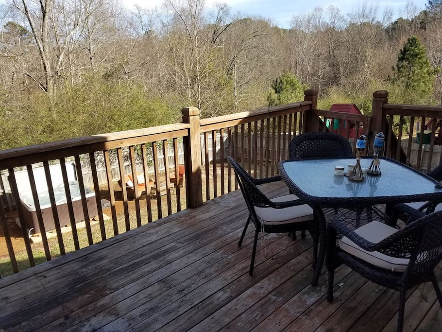 Patio deck with grill overlooking the hottub and outdoor lounge seating.