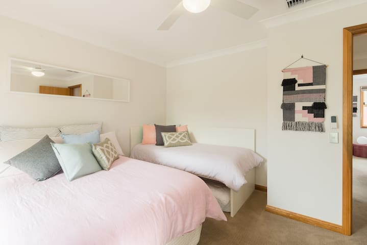 5th bedroom with a double bed and single, desk and balcony access.