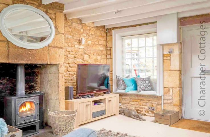 The lovely living room contains a large fireplace, with a lovely wood burning stove