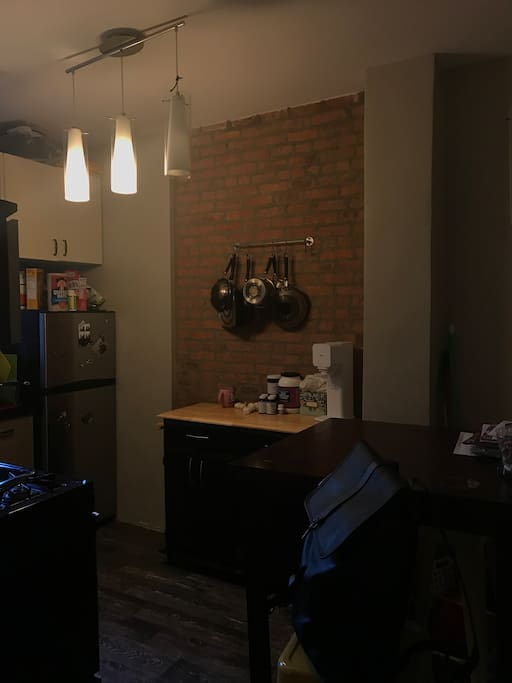 Exposed brick kitchen with stone flooring. Stainless steel amenities and fully stocked with latest appliances including Keurig, SodaStream, Bullet Blender and dishwasher.
