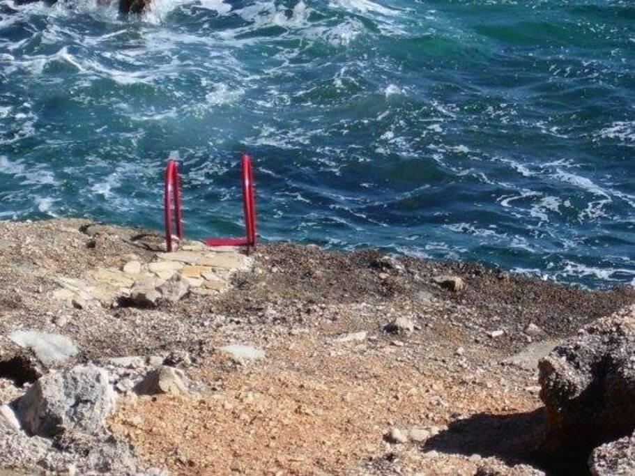 Spiaggia di scoglio con scaletta per discesa a mare