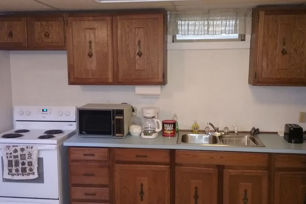 Spacious kitchen which has a stove, refrigerator, microwave, coffee maker, toaster, and kitchenware for your using pleasure.