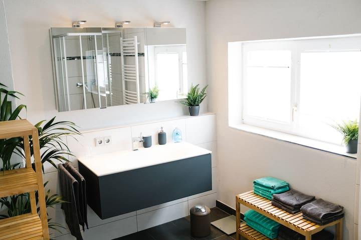 Badezimmer mit großem Waschbecken, Dusche, Ablagemöglichkeiten und ausreichend Handtüchern.