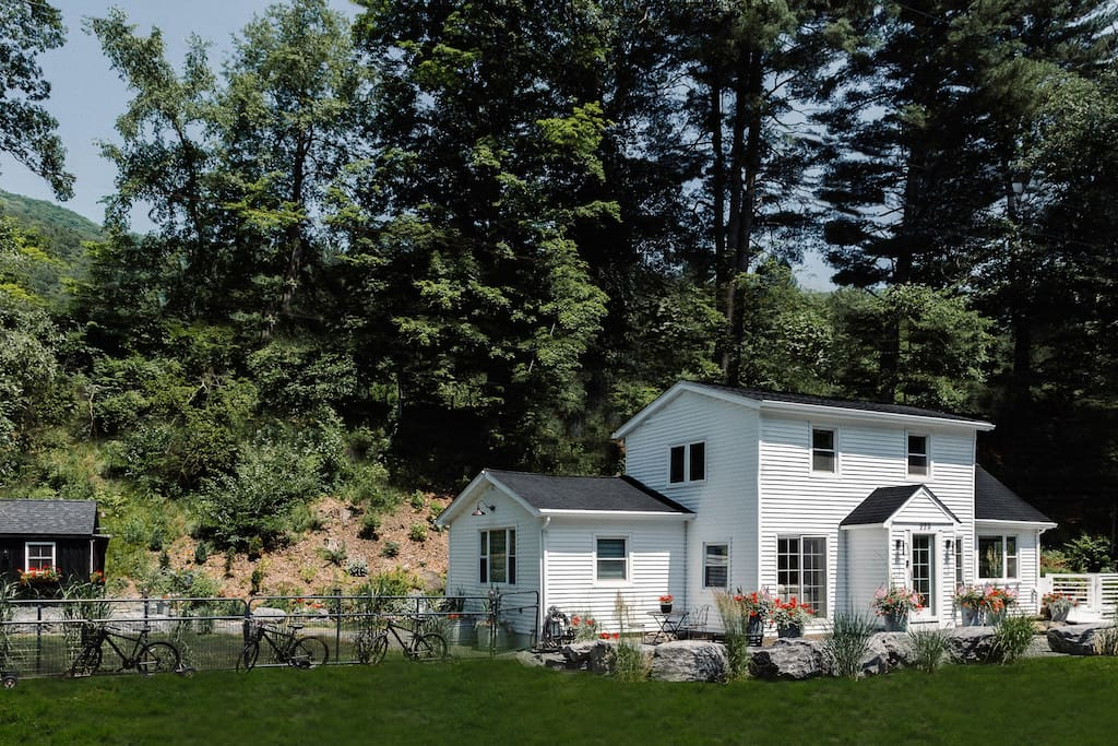 Historic Farmhouse Located on Main Street This farmhouse, built in the 1800s, sits on Main Street in a town outside of the Catskill Mountains. With tall trees and green pastures all around, the country home looks charming even at a distance.