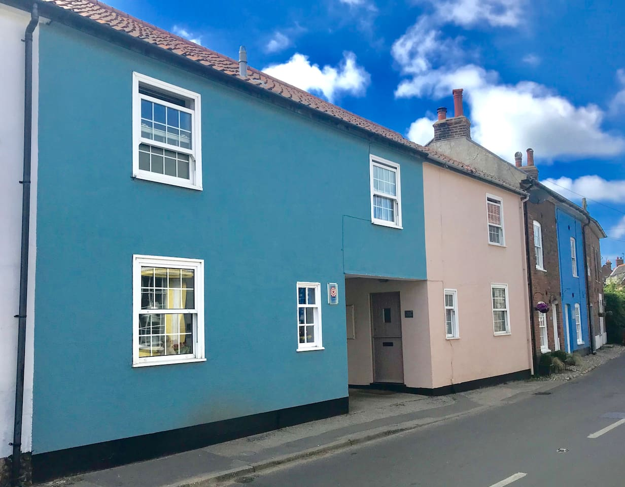 The house is a very pretty 'Stone Blue' colour. It was built in 1850 with the purpose of being a fisherman's cottage. The archway leads to the cottage's own off street parking space.