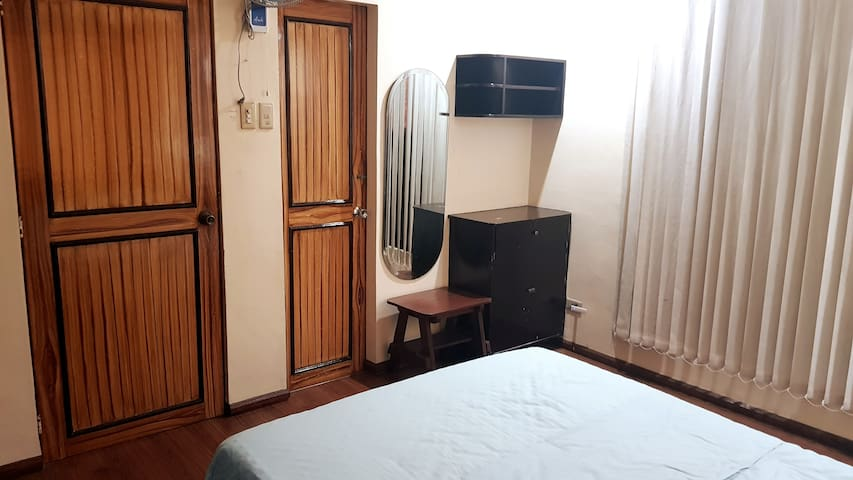 Double Bed, Side table, chair, Air-conditioning unit and sliding door/window to mezzanine