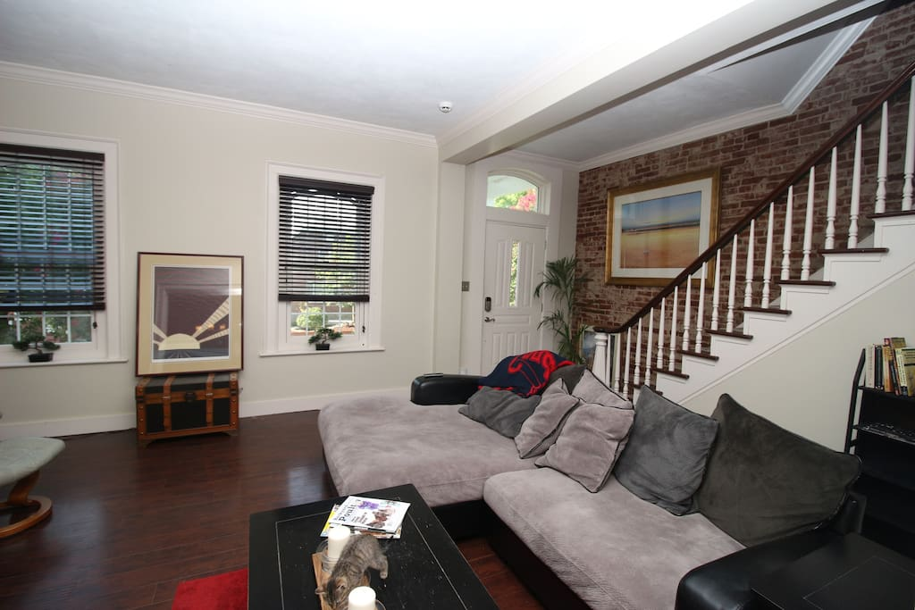 """Living room with exposed brick and 65"""" TV."""