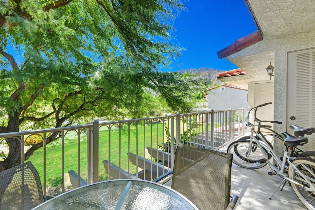 The back patio overlooks a grassy garden area and seats 4 people for dining.