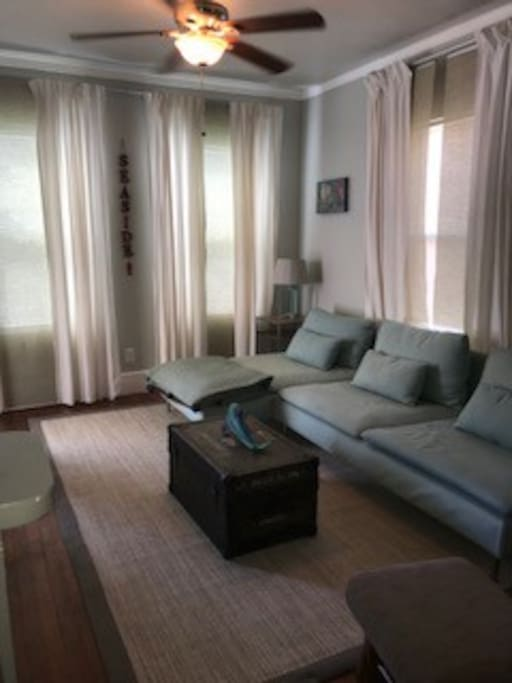 Beach themed living room has a flat screen TV and small couch than can also be used to sleep an extra guest if needed.