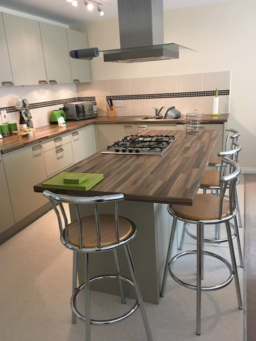 Island breakfast bar to seat 4 with built in gas hob and cooker hood.