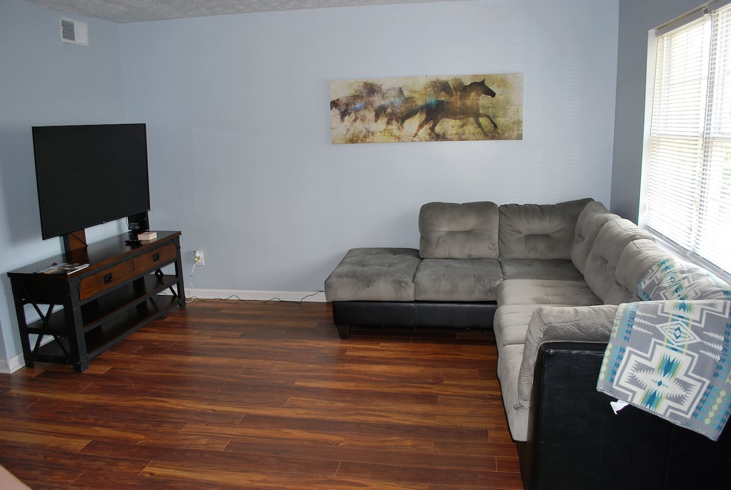 Spacious living room with all new furnishings. The TV is a smart TV, and we also provide Netflix.