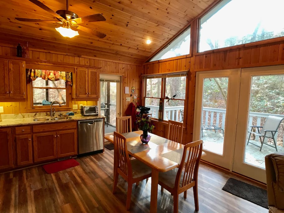 Dining area is open to kitchen and living area with views of the woods.