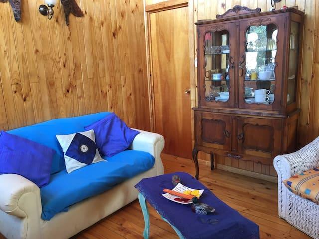 Living con dos sofá, más mueble con cristalería y menaje.
