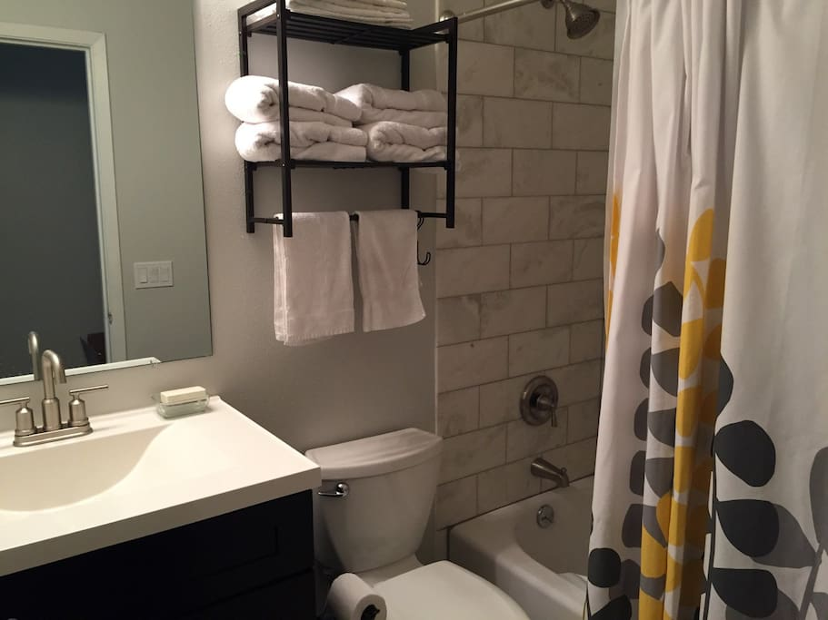 Private bathroom with granite tile shower, towels, other amenities.