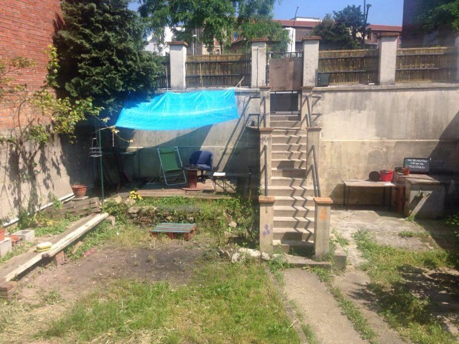 Le jardin dispose d'une petite terrasse ombragée pour manger dehors