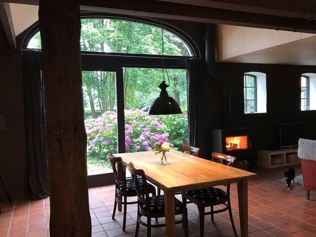 Woon-/eetkamer met hoge glazen pui en prachtig uitzicht, houtkachel, eethoek en zithoek