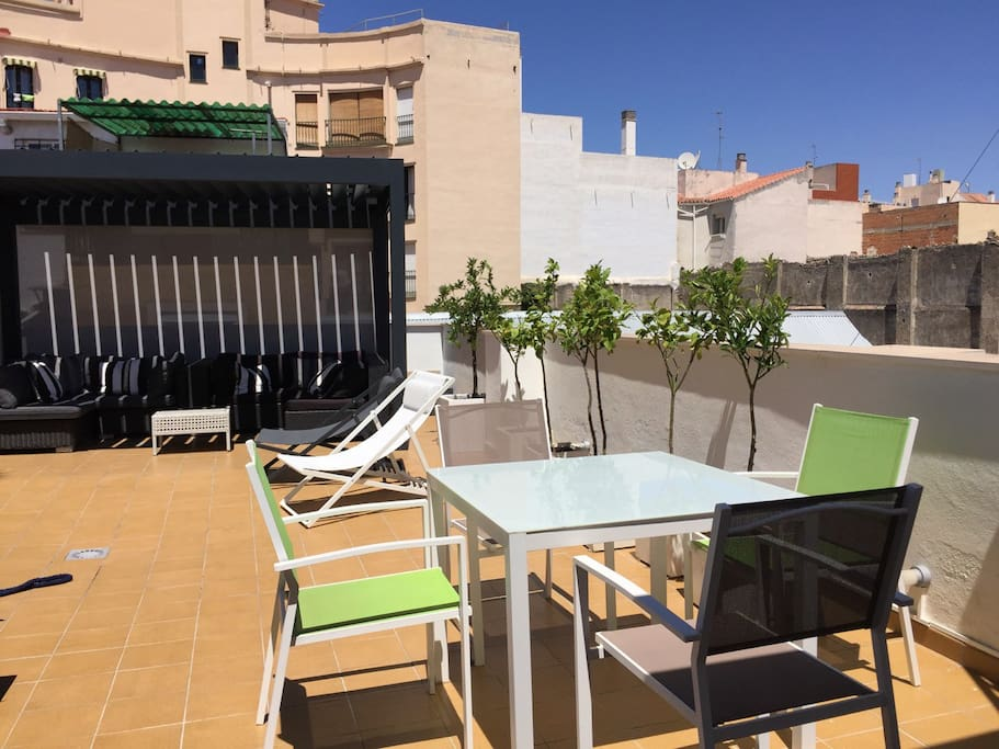 Large private roof terrace with table for outdoor dining.