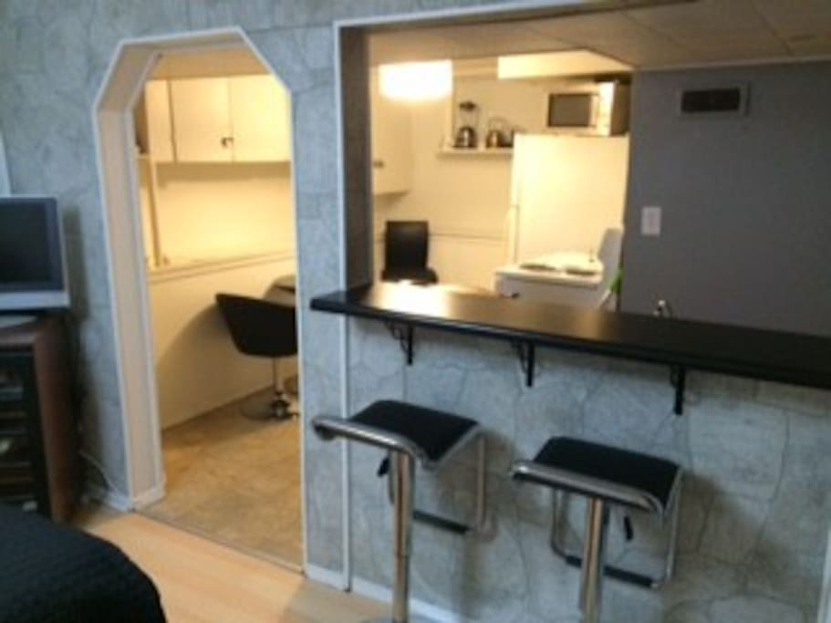Open counter into Kitchen with black chrome bar stools