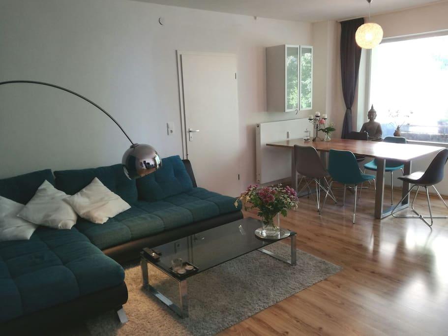 Das Wohnzimmer mit Couch und großem Esstisch.