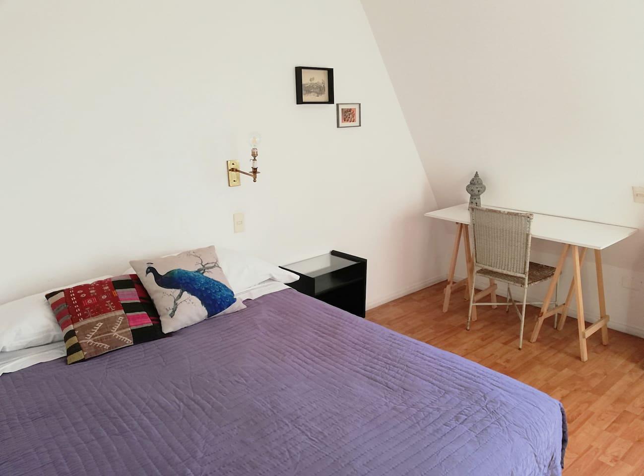 Pieza luminosa, cama de 2 plazas, velador y sencillo escritorio.