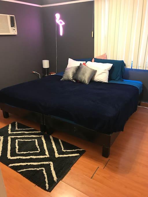 Cama king size con juego de sábanas o individuales para huéspedes que deseen dormir separados.