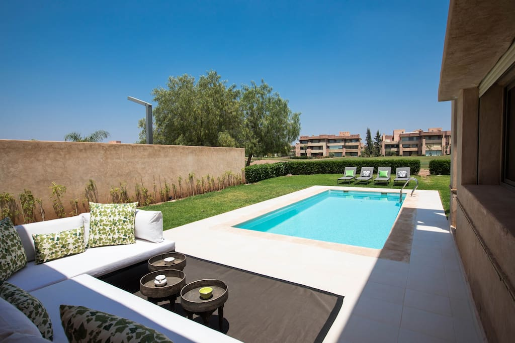 view of the pool and the golf course from the lounging area. Direct access to the golf course from the garden.
