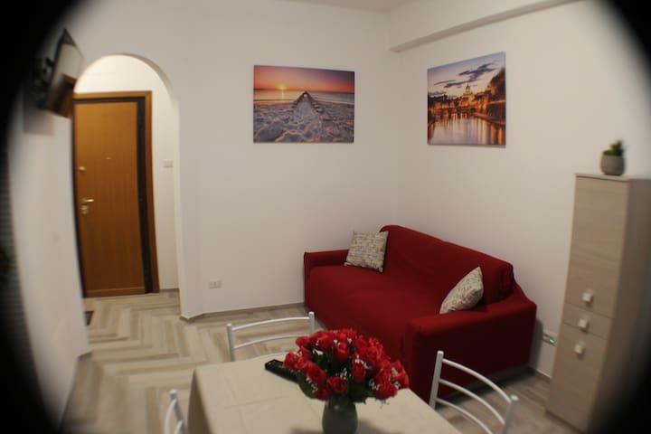 Salone con divano quatro posti, tv 32' e tavolo...