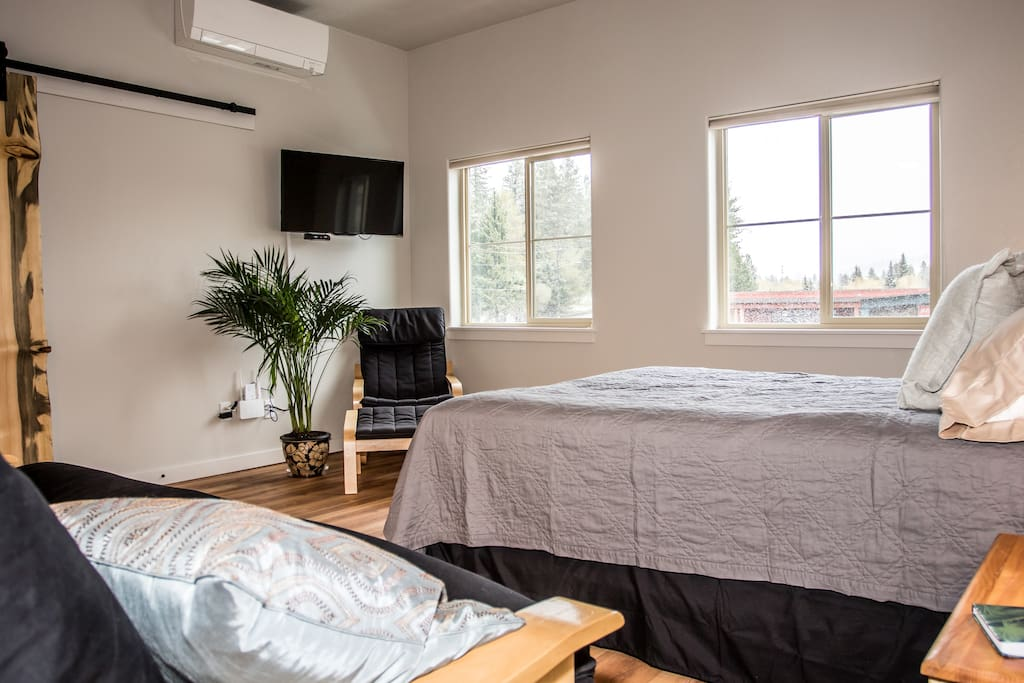 Queen size bed and futon with a smart TV and cable