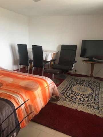 Schlafzimmer im unteren Stock mit Doppelbett und Tisch und Fernseher