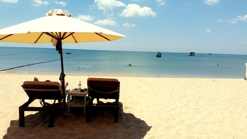 Relax on comfortable sunbeds on your own private beach.