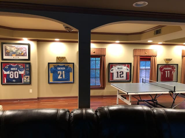 Sports lovers paradise living space with leather recliners, ping pong, and darts.