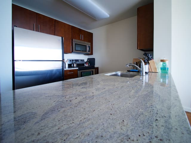 Spacious kitchen with dark wood cabinets, stainless steel appliances, and granite countertops.