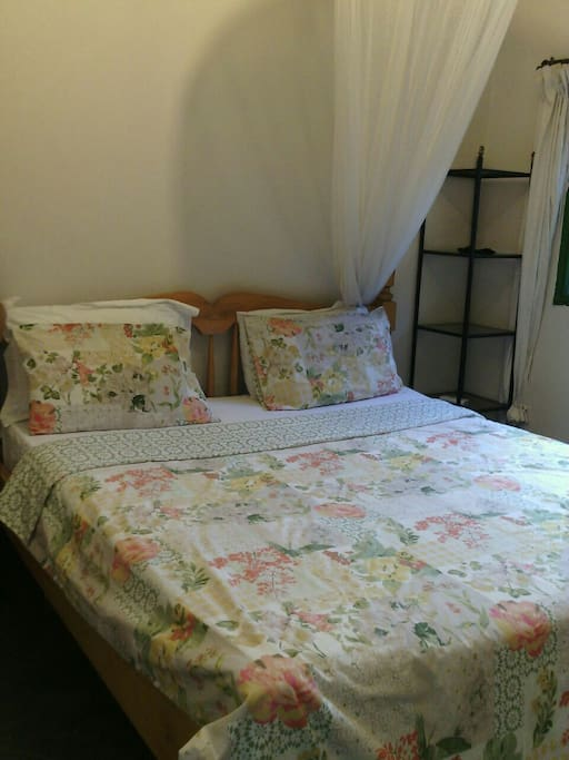 Bedroom has a large comfortable king size bed with a mosquito net, a sofa and shelves for hanging and keeping clothes.